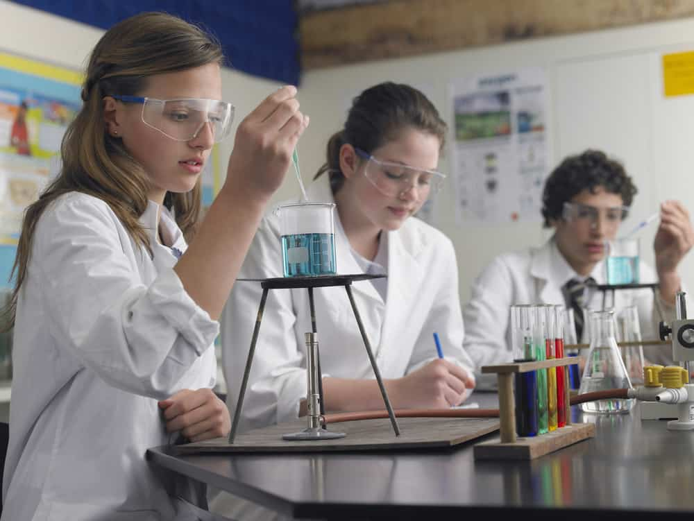 High school students doing experiment in science class