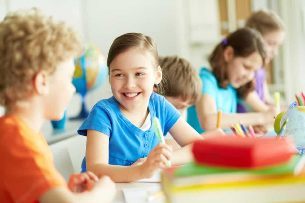 Happy children working together at school.