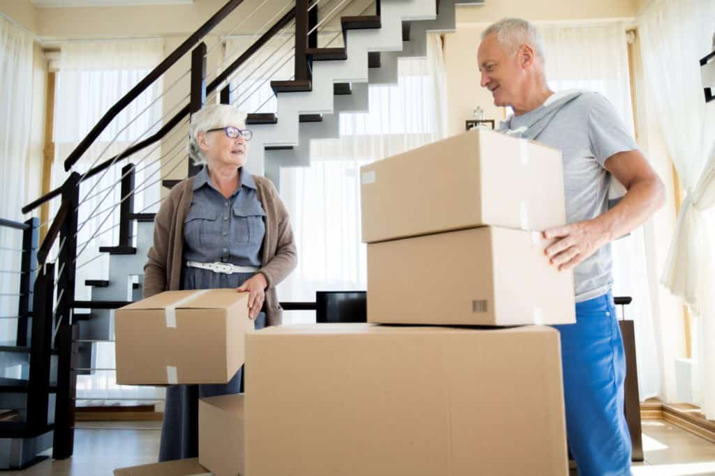Senior couple handling boxes